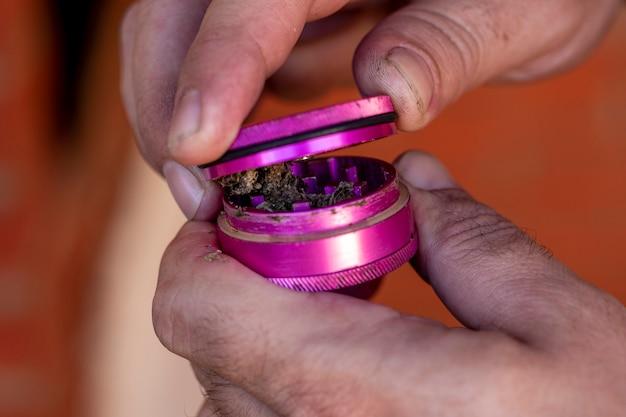 Uomo che macina marijuana per fare una canna.