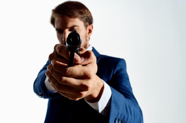 Pistola dell'uomo nelle mani dello sfondo chiaro dell'agente delle emozioni della mafia