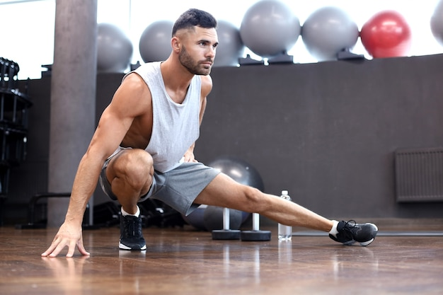 Uomo in palestra facendo esercizi di stretching sul pavimento.