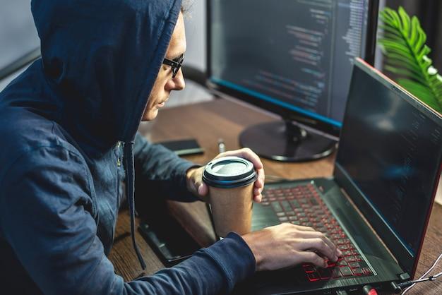 L'uomo hacker in una cappa sta programmando il codice del virus su un laptop