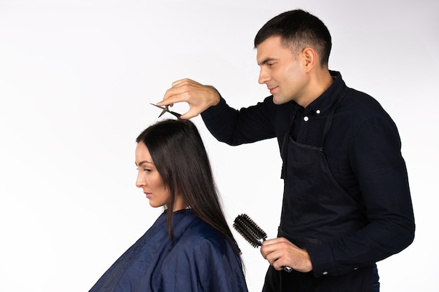 Il parrucchiere uomo taglia i capelli lunghi della donna bruna sfondo bianco isolato