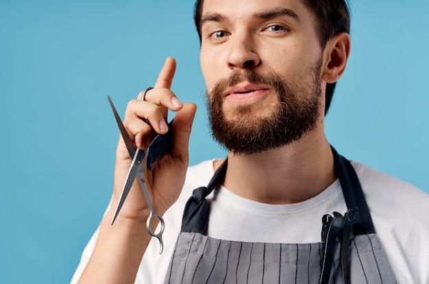 Un parrucchiere uomo in un grembiule grigio si fa i capelli su uno sfondo blu forbici pettine. foto di alta qualità