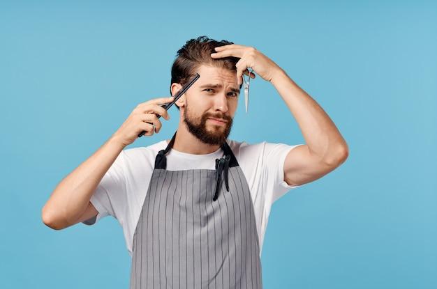 Un parrucchiere uomo in un grembiule grigio si fa i capelli su un pettine forbici muro blu.
