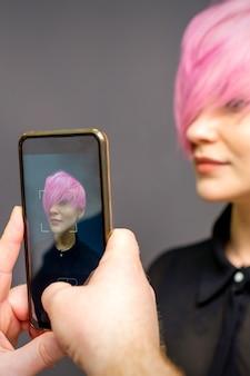 Mani dei parrucchieri dell'uomo che scattano foto sullo smartphone della sua acconciatura rosa corta del cliente