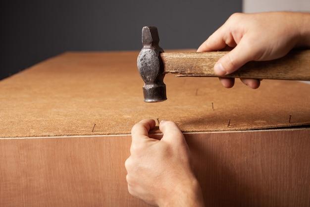 Un uomo martella i chiodi in un armadio.