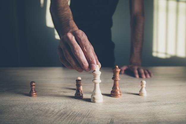 Scacchi della mano dell'uomo sulla tavola di legno