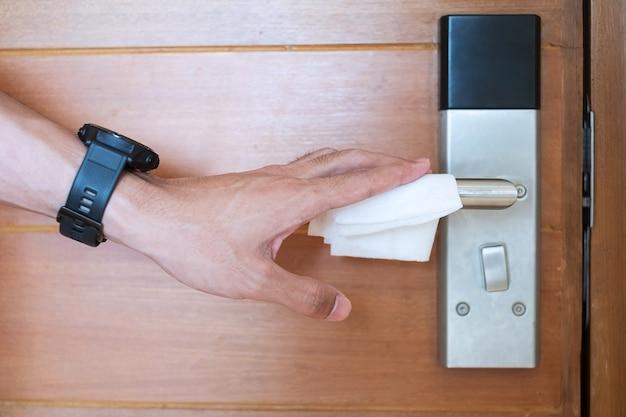 Maniglia della porta digitale per la pulizia della mano dell'uomo con un panno umido, protezione coronavirus o malattia da virus corona (covid-19) nella stanza pubblica. superficie pulita, stile di vita, viaggi sicuri e nuovo concetto normale