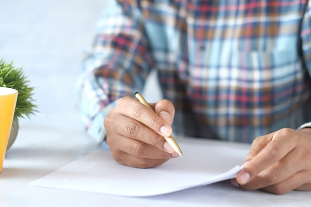 Mano dell'uomo nella scrittura o nella firma della penna stilografica su carta