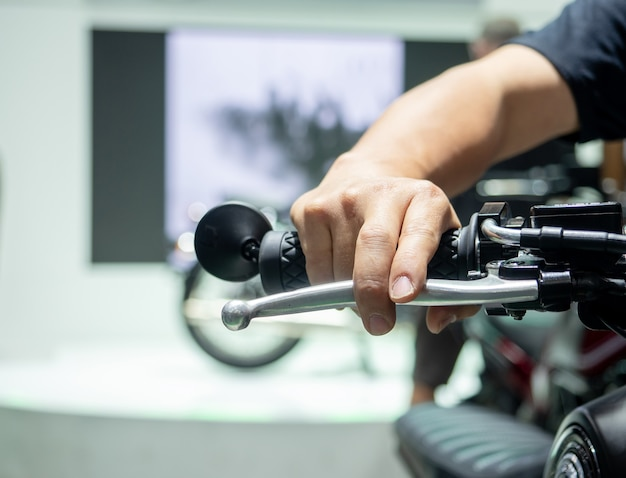 Mano dell'uomo alla maniglia della motocicletta sfocatura dello sfondo, presa a mano della barra della maniglia della motocicletta