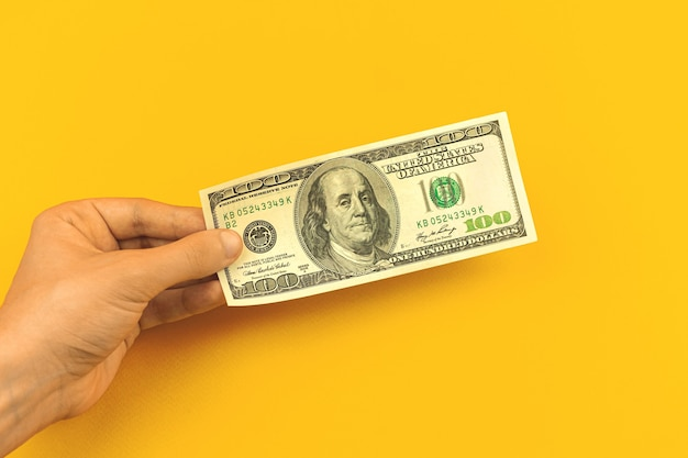 Man mano tenere una banconota da cento dollari su sfondo giallo del tavolo da ufficio, concetto di deposito bancario