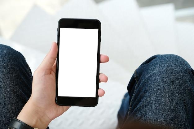 Equipaggi la mano che tiene lo smart phone nero con lo schermo in bianco su fondo per derisione su