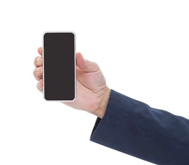 Equipaggi la mano che tiene lo smartphone nero con lo schermo bianco in bianco isolato su fondo bianco