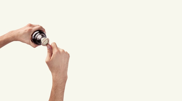 Mano dell'uomo che tiene una bottiglia di birra vista dall'alto in uno sfondo bianco chiaro con spazio di copia