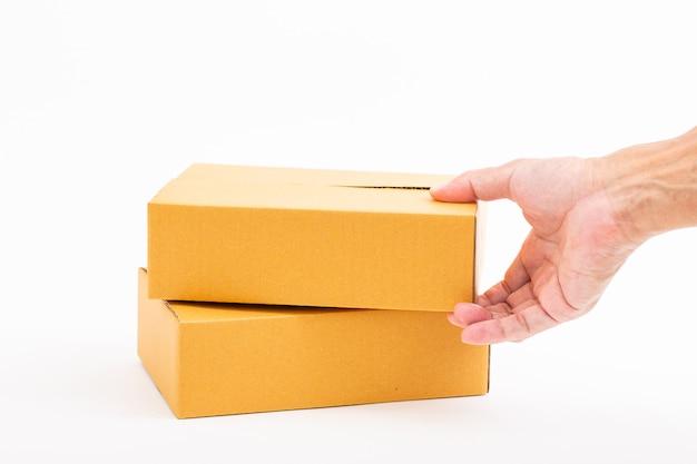 Man mano che tiene brown riciclare la scatola di carta su bianco