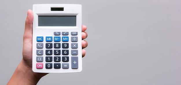 Calcolatrice della tenuta della mano dell'uomo su fondo grigio con lo spazio della copia