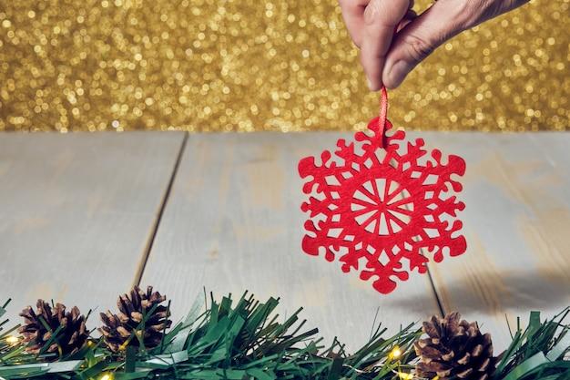 Mano dell'uomo che tiene l'ornamento rosso del fiocco di neve di natale con la tavola di legno delle pigne e fondo d'oro lucido non focalizzato