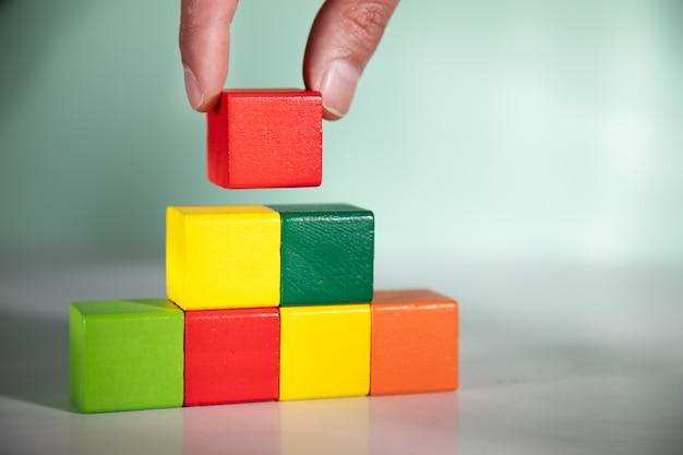 Man mano che tiene il blocco del cubo di colore