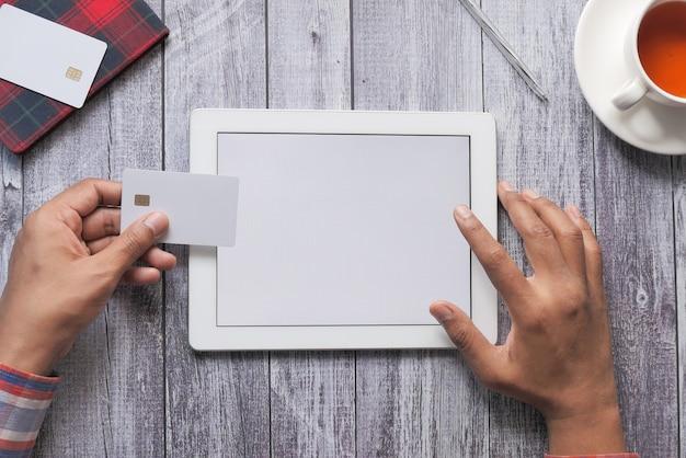 Man mano che tiene la carta di credito e utilizzando la tavoletta digitale acquisti online.