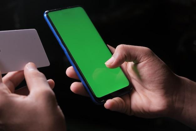 Man mano che tiene la carta di credito e utilizzando smart phone acquisti online