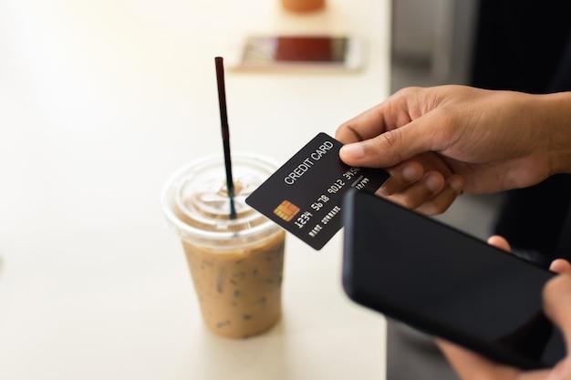 Man mano che tiene la carta di credito con lo smartphone nella caffetteria.
