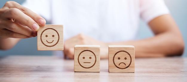 Man mano che tiene il blocco del viso emozione. il cliente sceglie emoticon per le recensioni degli utenti. valutazione del servizio, classifica, recensione del cliente, soddisfazione, valutazione e concetto di feedback