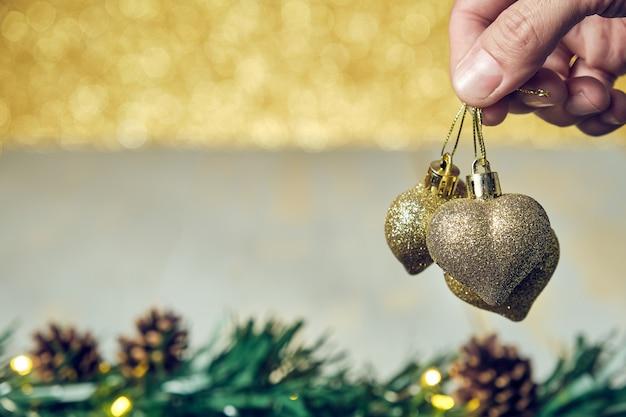 Mano dell'uomo che tiene l'ornamento dorato dei cuori di natale con il tavolo di legno delle pigne e lo sfondo dorato lucido non focalizzato