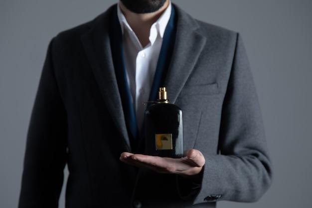 Man mano che tiene la bottiglia di profumo