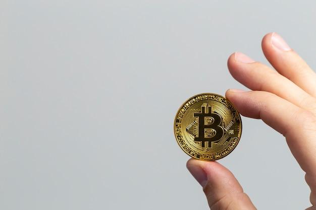 Man mano che tiene un bitcoin fisico davanti a uno sfondo bianco