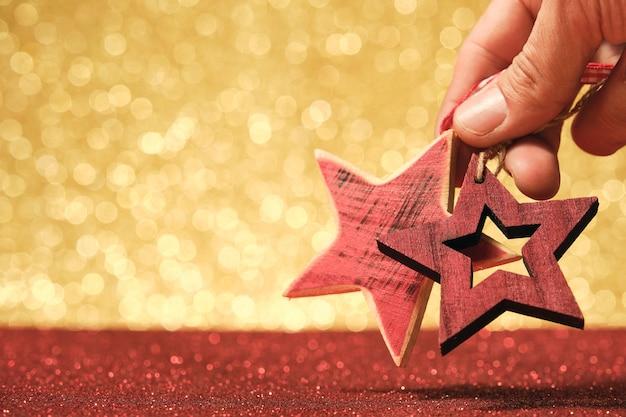 Mano dell'uomo che tiene l'ornamento di natale in legno a forma di stella rossa su sfondo rosso e oro lucido sfocato