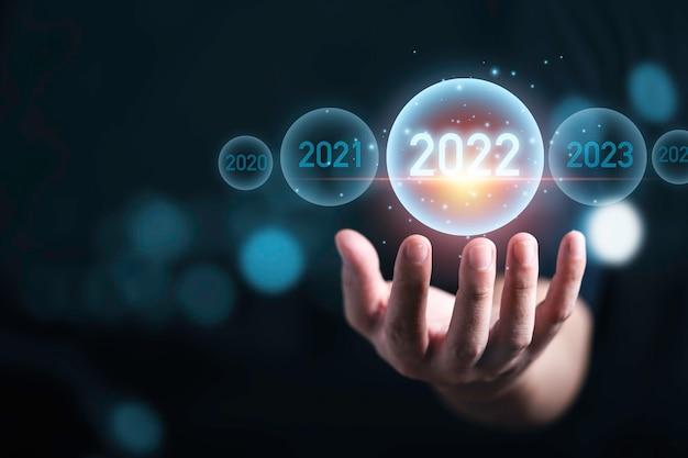 Mano dell'uomo che tiene l'anno 2022 virtuale con bokeh blu per la preparazione di buon natale e felice anno nuovo concetto.
