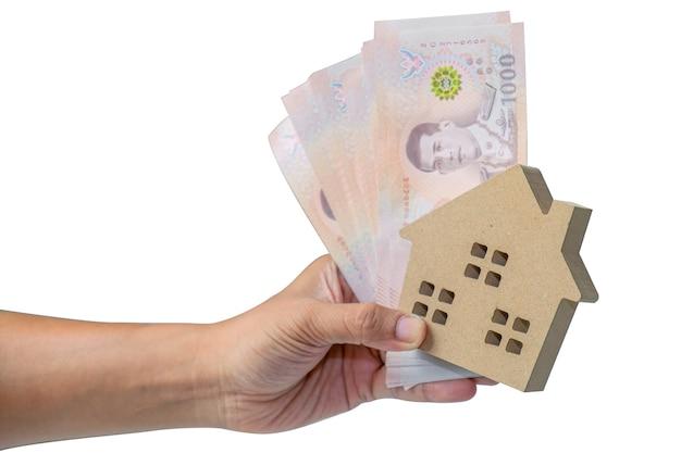 Man mano che tiene il modello di casa in legno e soldi delle banconote della thailandia