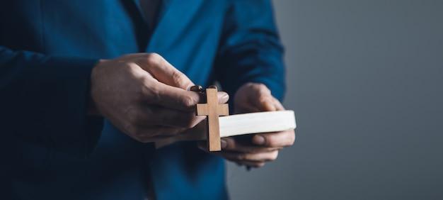 Man mano sacra bibbia e croce di legno