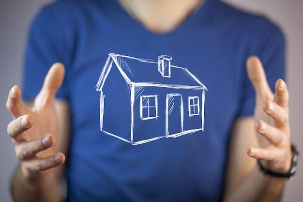 Modello di casa della mano dell'uomo sullo schermo