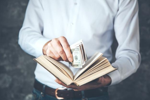 Soldi della mano dell'uomo con il libro su sfondo scuro