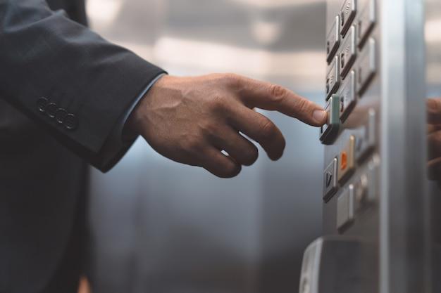 Impiegato di mano dell'uomo in giacca e cravatta premere il pulsante dell'ascensore con il dito. uomo d'affari in
