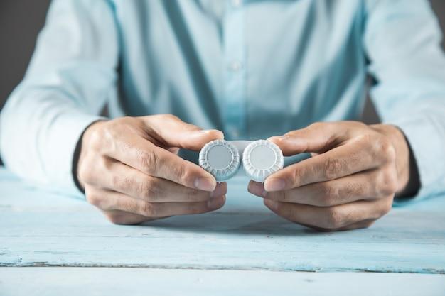 Lenti ottiche della mano dell'uomo sul tavolo blu