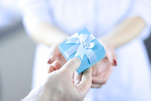 La mano dell'uomo passa la confezione regalo alla sorpresa della donna per il concetto di donna