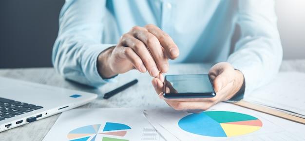 Telefono della mano dell'uomo con il documento sulla scrivania
