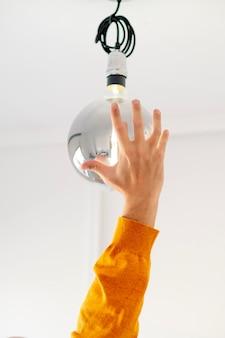 Man mano che immette un gigante moderno lampadina con muro bianco