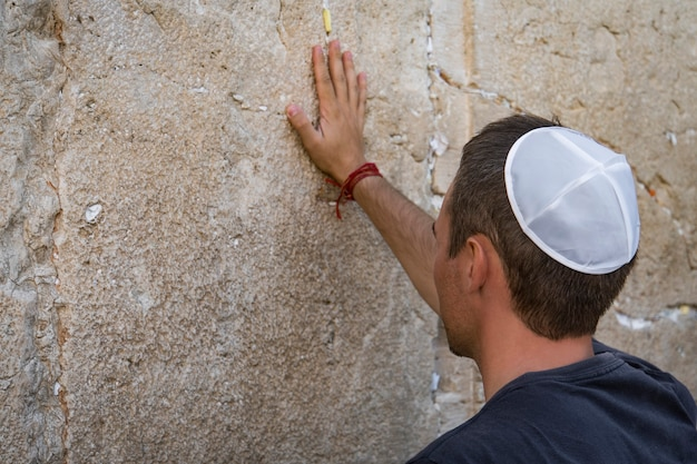 Man mano e carta da preghiera sul muro occidentale, il muro del pianto il luogo del pianto è un antico muro di pietra calcarea nella città vecchia di gerusalemme. secondo tempio ebraico di erode il grande.