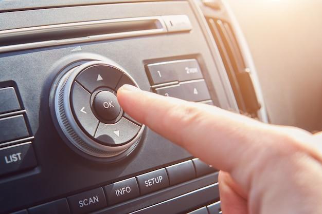 Man mano premere il pulsante ok sul pannello in macchina. driver che accende il sistema multimediale. viaggiare in macchina. vista ravvicinata con il fuoco selettivo.