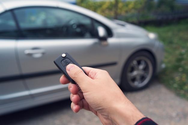 La mano dell'uomo preme un pulsante sul telecomando dell'auto contro la sfocatura dell'auto. il nuovo proprietario di un veicolo sblocca l'acquisto. il concessionario di automobili mostra e apre i veicoli. noleggio auto. sistema di allarme di un motore.
