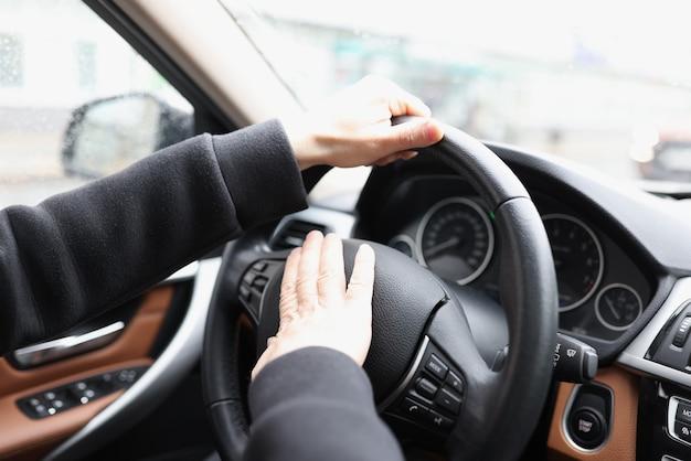 La mano dell'uomo preme il clacson sul volante dell'auto
