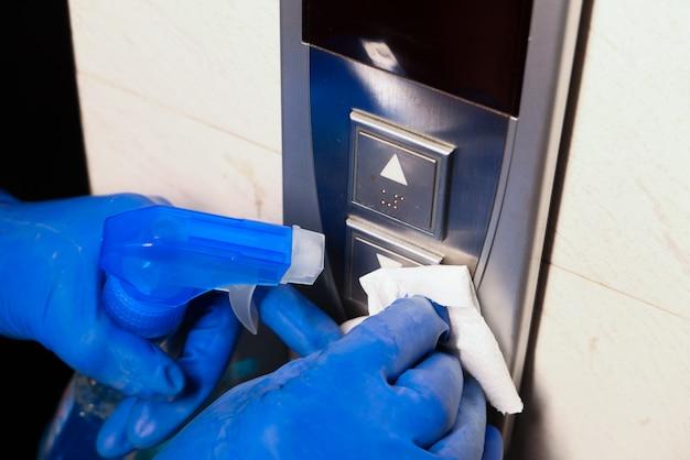Man mano in guanti protettivi che disinfettano i pulsanti dell'ascensore.