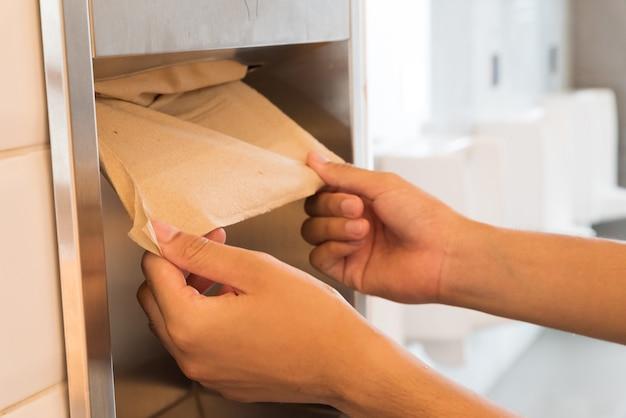 Equipaggi la mano che tira un tessuto marrone dalla scatola del tessuto nel bagno.