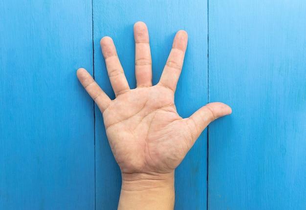 La mano dell'uomo si è alzata contro su fondo di legno blu
