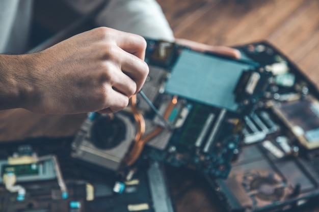 Cacciavite a mano uomo con computer sulla scrivania