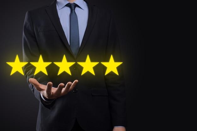 Man mano che mostra su cinque stelle eccellente rating.pointing simbolo a cinque stelle per aumentare la valutazione della società. rivedere, aumentare la valutazione o la classifica, la valutazione e il concetto di classificazione.