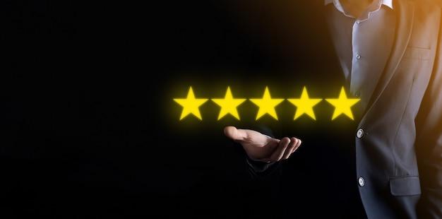 Man mano che mostra sulla valutazione eccellente a cinque stelle. indicando il simbolo a cinque stelle per aumentare la valutazione della società
