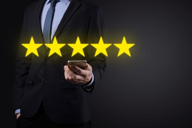 Man mano che mostra sulla valutazione eccellente a cinque stelle. indicando il simbolo a cinque stelle per aumentare la valutazione
